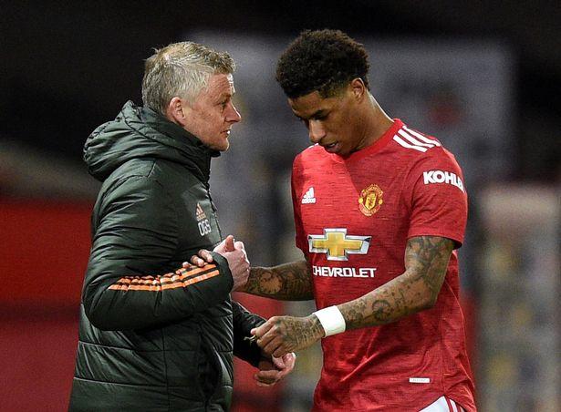 Marcus Rashford berjabat tangan dengan manajer Manchester United Ole Gunnar Solskjaer