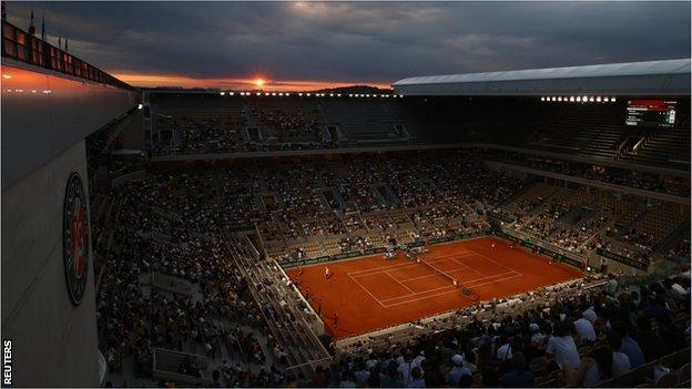 Matahari terbenam di atas Stadion Philippe Chatrier saat Novak Djokovic menghadapi Matteo Berrettini